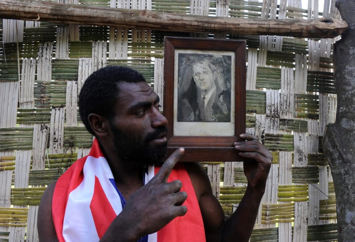 Sikor Natuan, the son of the local chief, holds two official portraits of Britain's Prince Philip in front of the chief's hut in the remote village of Yaohnanen on Tanna in Vanuatu.