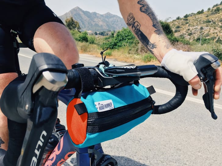 A tattooed cyclist rides a bike equipped with a small blue bag under the handlebars.