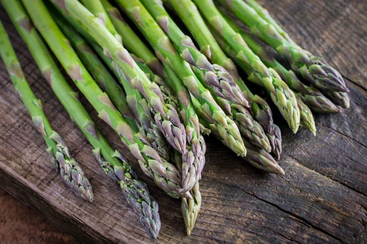 A selection of asparagus stalks on wood