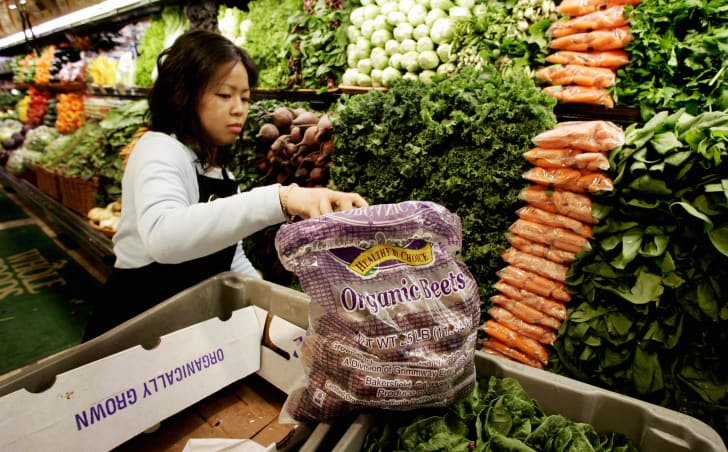 Whole Foods worker stocking vegetables