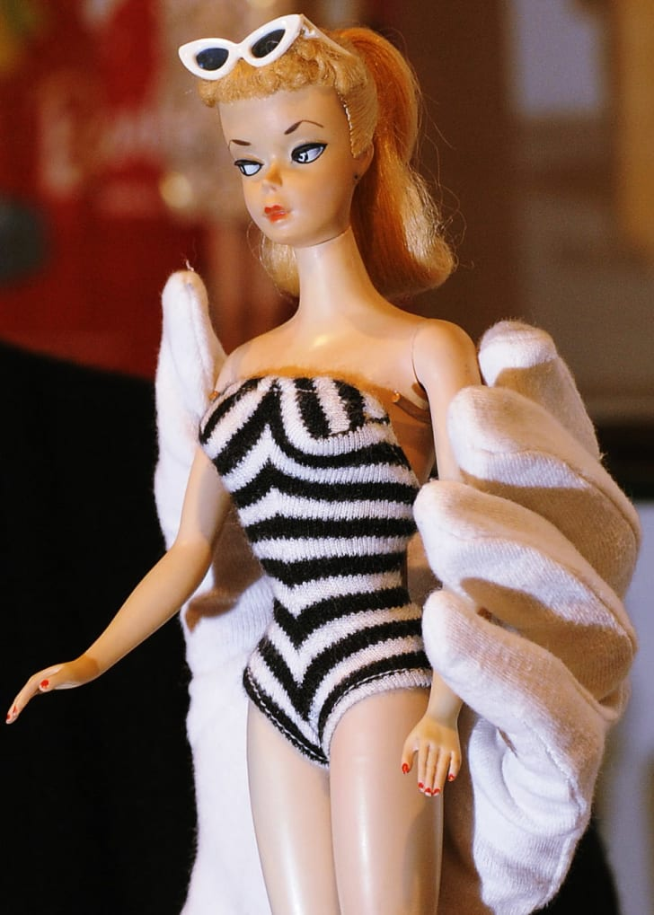A gloved hand holding a vintage Barbie doll wearing a black and white knit bathing suit.