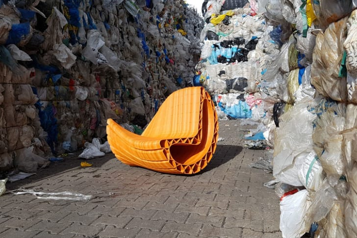 A plastic chair is surrounded by trash