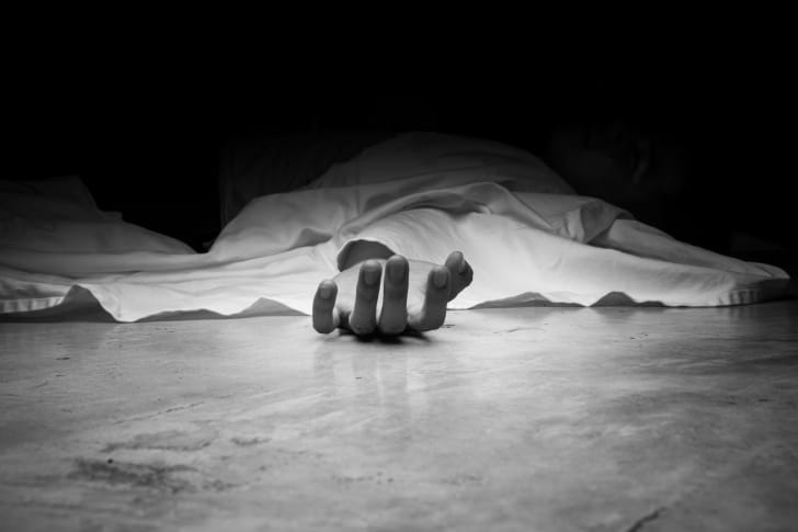 Corpse under sheet with hand sticking out
