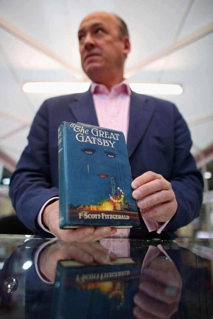 A bookseller holding a first edition of The Great Gatsby at the London International Antiquarian Book Fair in 2013