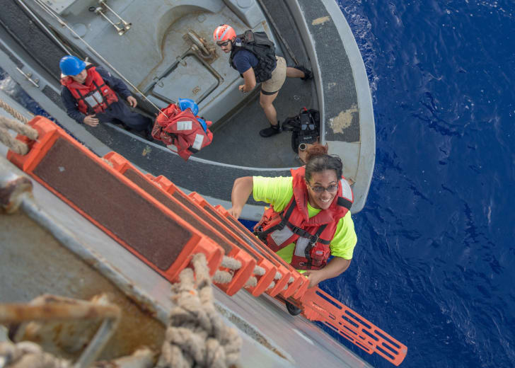 Tasha Fuiaba, an American mariner who had been sailing for five months on a damaged sailboat, climbs the accommodation ladder to board the USS Ashland.