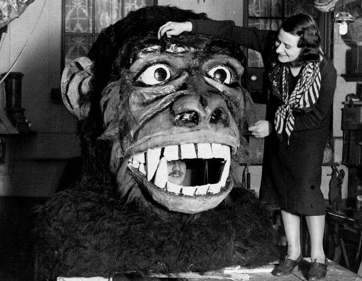 A 1933 photo of a man inside the mouth of a monkey head made by a stage props company
