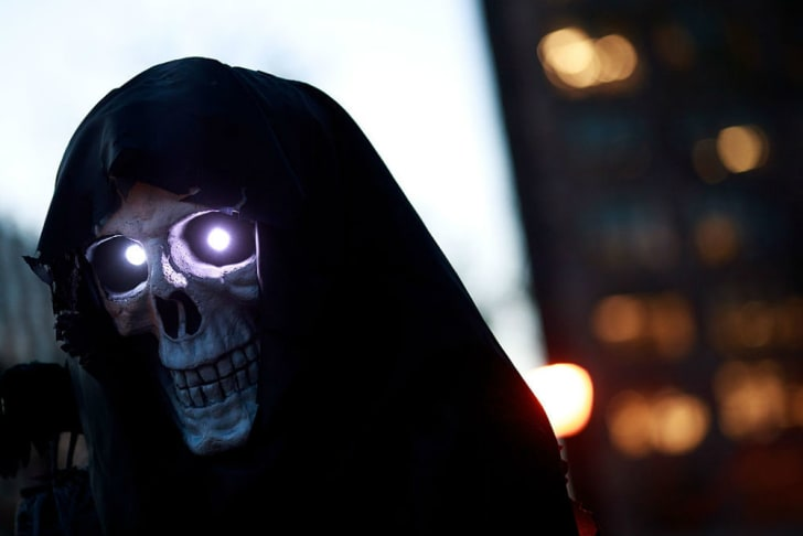 A person appears in a skull costume with glowing eyes for Halloween