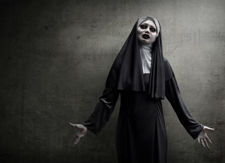 A woman models a scary nun costume for Halloween