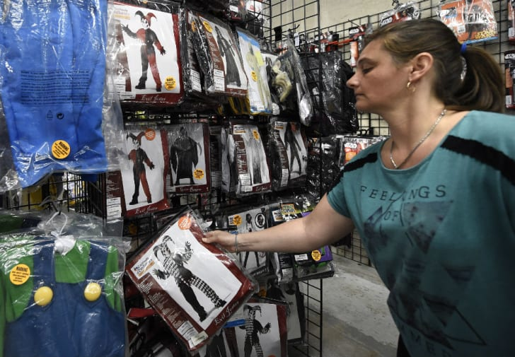 A woman shops for costumes in a retail store