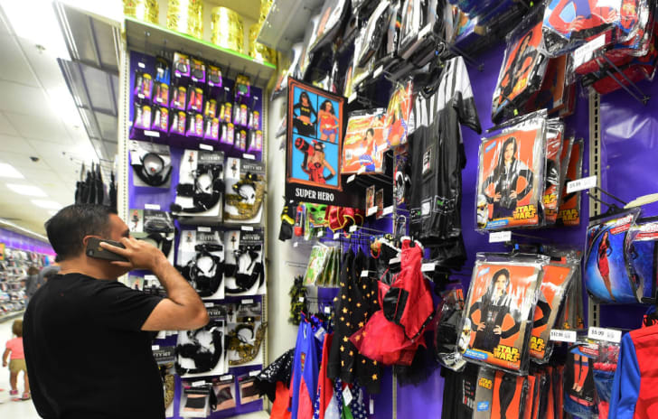 A man shops for Halloween costumes in a retail store
