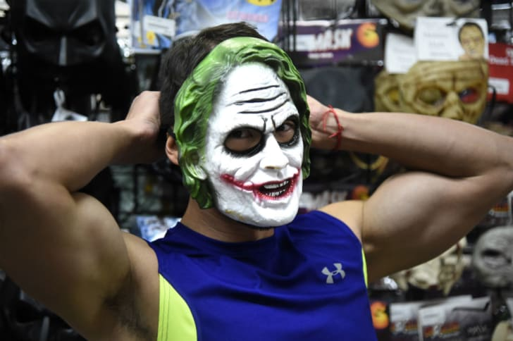 A man tries on a Joker mask at a retail store