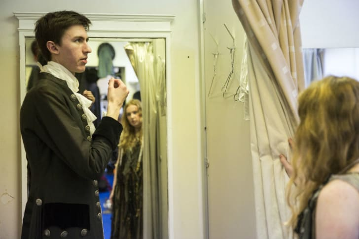 A man models a costume in front of a mirror