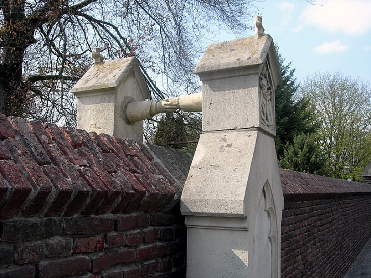 "A close-up photograph of two graves in Roermond, the Netherlands, known as Het graf met de handjes, or ""Grave with the little hands."""