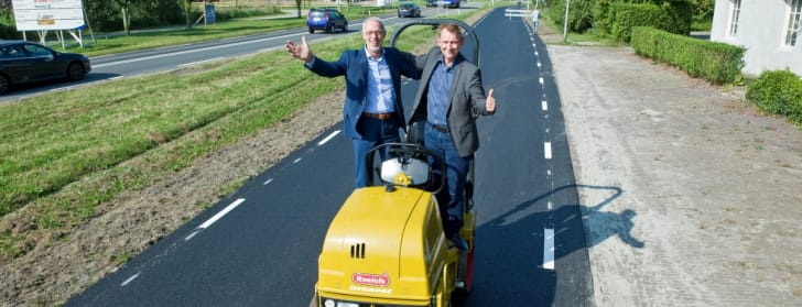 Two men stand on a paving machine in front of an asphalt bike lane.