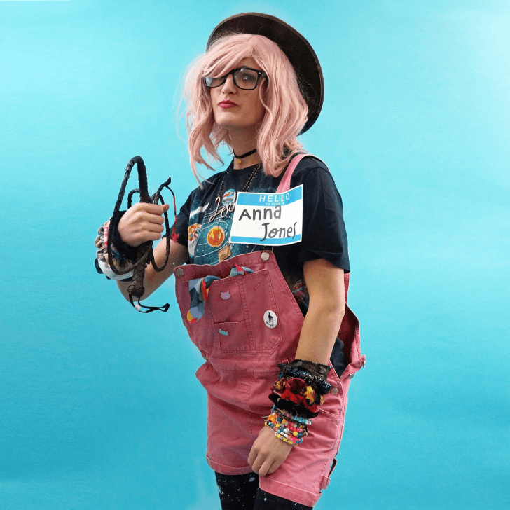 "A woman in pink overalls, carrying a whip, wearing a hat and a nametag that says ""Anna Jones."""