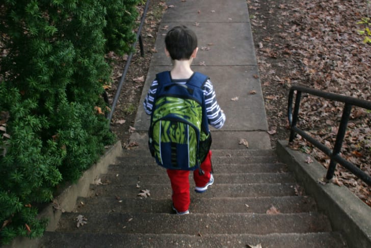 A child with a backpack walks down a flight of stairs