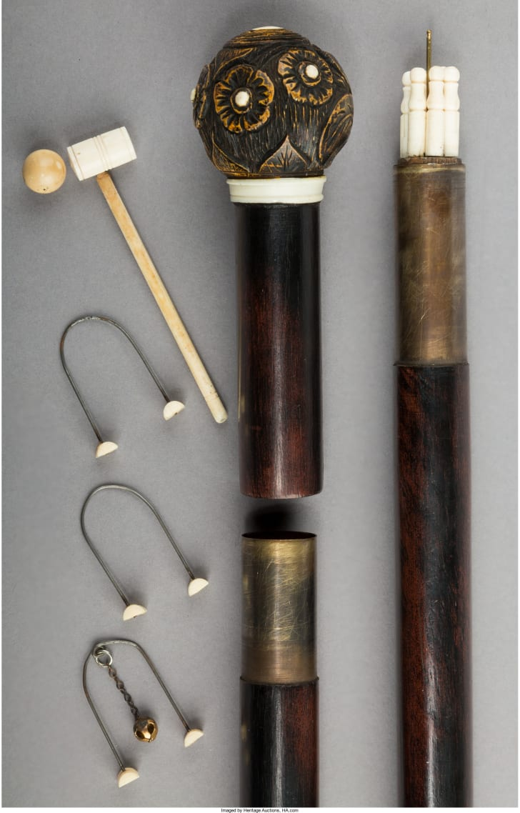 Cane with miniature croquet set.
