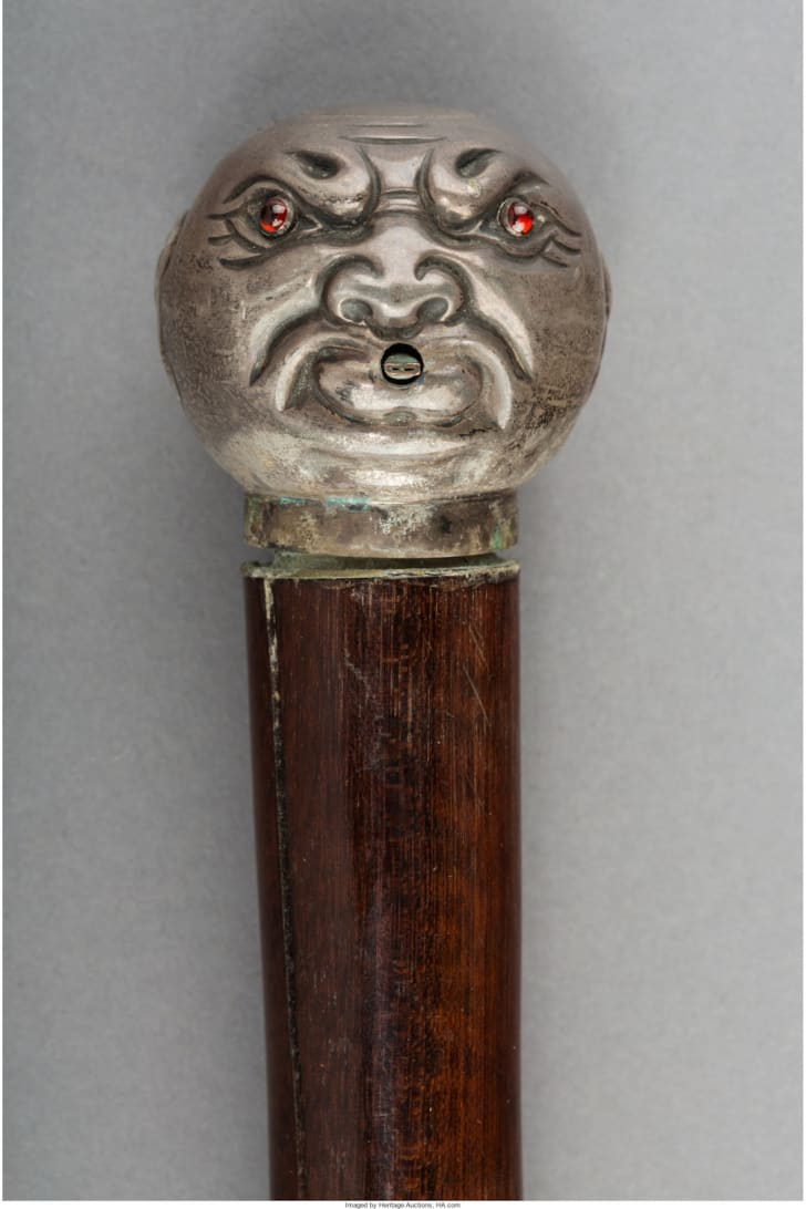 Cane handle shaped like a face.