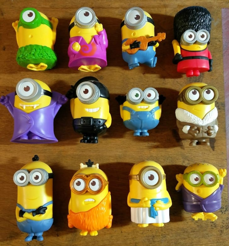 Rows of McDonald's Minion happy meal toys on a wooden background.