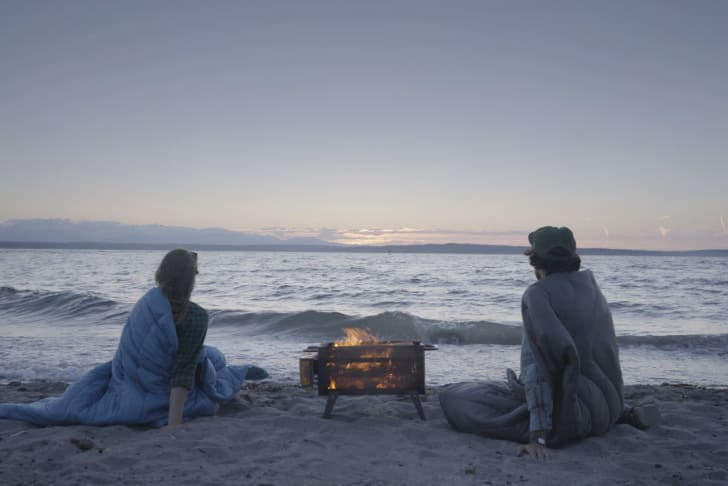 Couple sitting by a firepit on the beach.