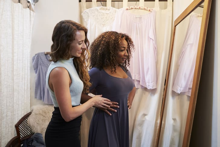 A young woman helping another woman assess a dress in a dressing room