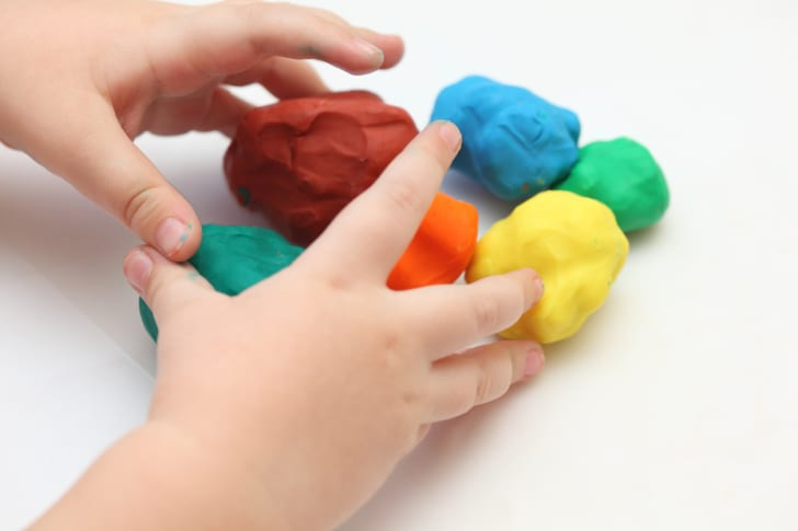 Photo of child's hands playing with Play-Doh clay