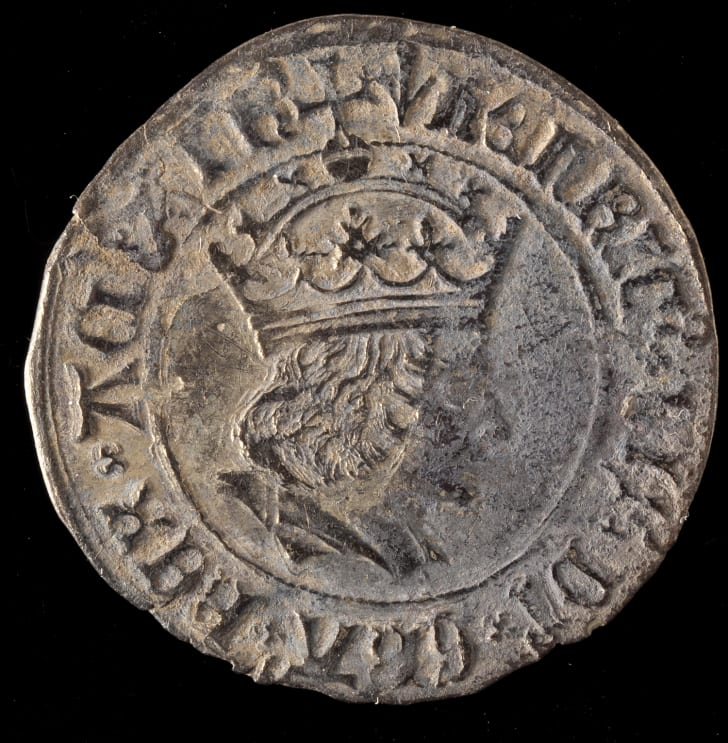 A primary school caretaker with a metal detector discovered a hoard of 128 silver Medieval-era coins, which were buried underneath the playground at the Warkworth Church of England Primary School in Warkworth, England.