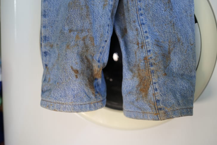 The ankles of a pair of mud-splattered blue jeans hanging in front of a washing machine.