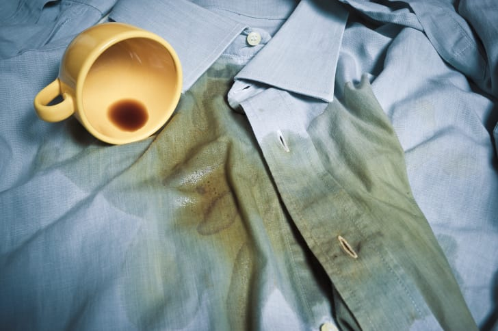 A yellow coffee cup tipped sideways, sitting on top of a blue dress shirt. The coffee has spilled all over the blue shirt.
