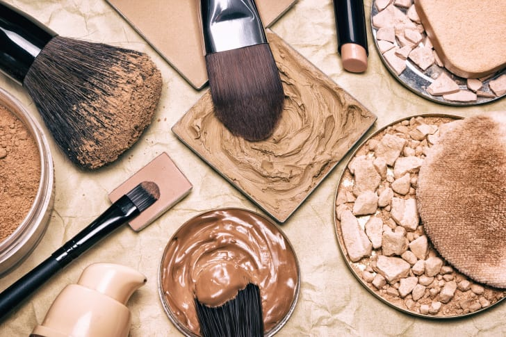 Various circular and square pans containing liquid and powder makeup, with brushes dipping into some of them.