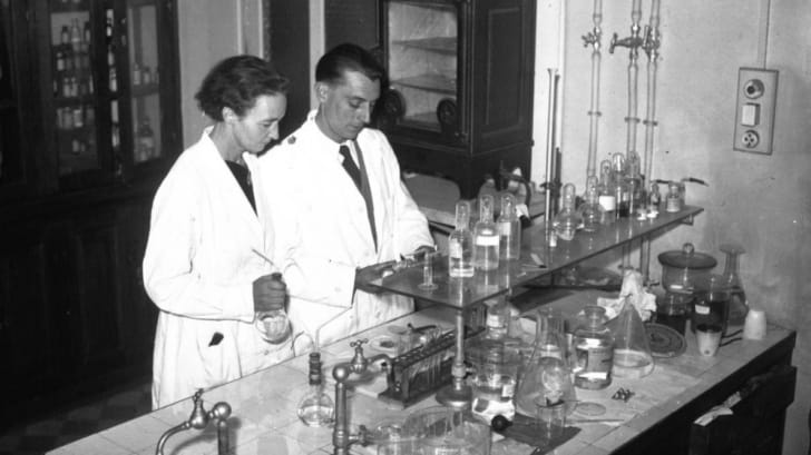 Black and white photo of Irène and Fréderic Joliot-Curie working side by side in their laboratory.
