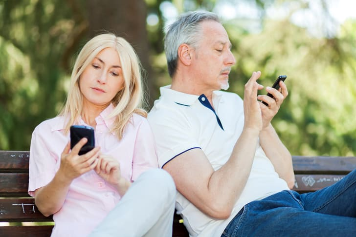 An older man and a woman looking bored and each on their phones