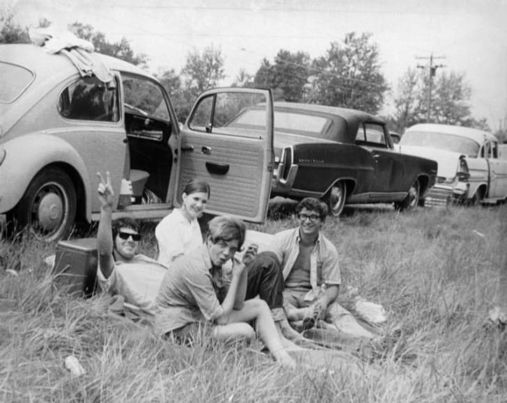 Attendees at Woodstock sit near their car