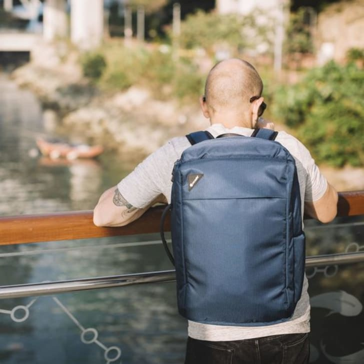 A man wearing a Pacsafe backpack looks over a bridge onto a river