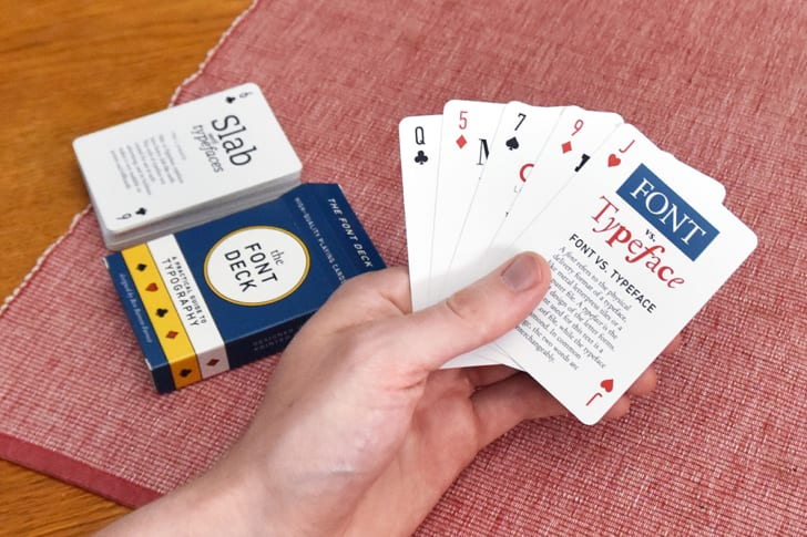 A male hand holds fanned-out cards next to a Font Deck box and a stack of playing cards.