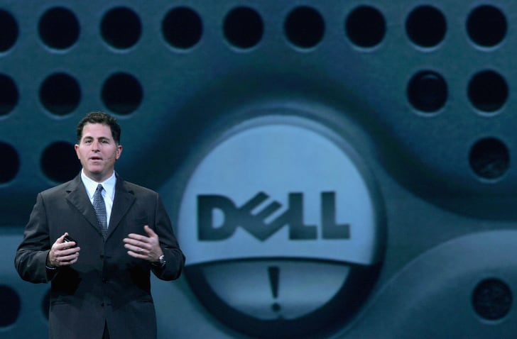 "A man in a suit (Michael Dell) speaking on a stage in front of a large Dell logo - a circle with the word ""DELL"" inside."