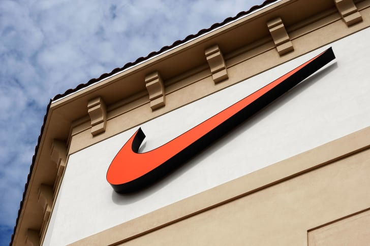 An orange Nike Swoosh logo on the outside of a retail store.