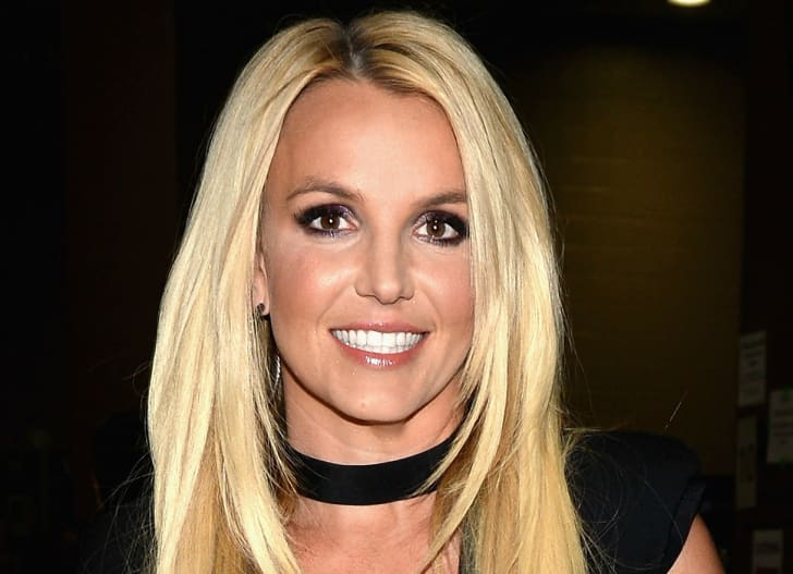 A blonde woman (performer Britney Spears) wearing a black choker necklace is smiling directly at the camera.