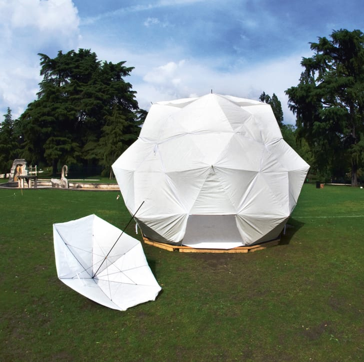 A white structure made of umbrellas sits in a park with a single white umbrella opened in front of it.