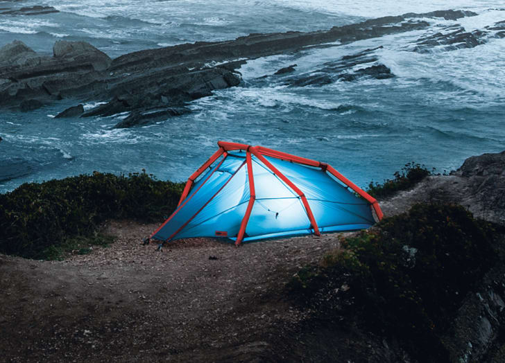 A blue tent illuminated from the inside sits on the edge of a rocky beach.