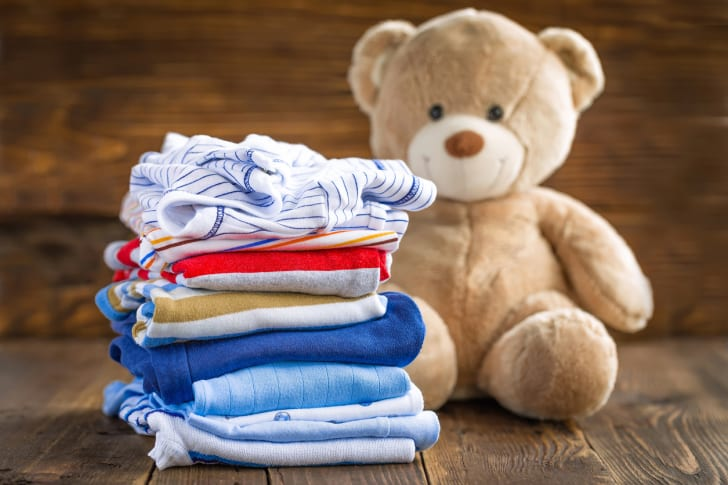 A stack of folded baby clothing sitting on a table next to a brown teddy bear.