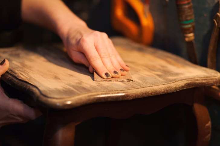 Woman restoring a piece of old furniture