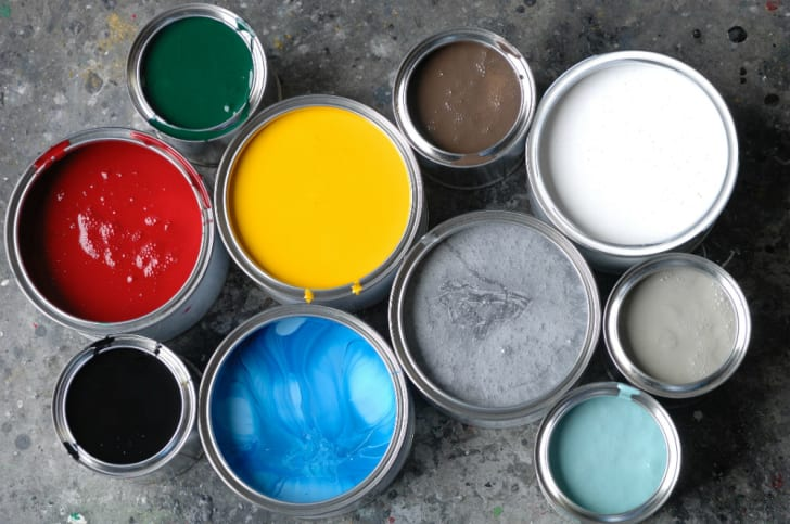 Cans of paint are arranged on the floor