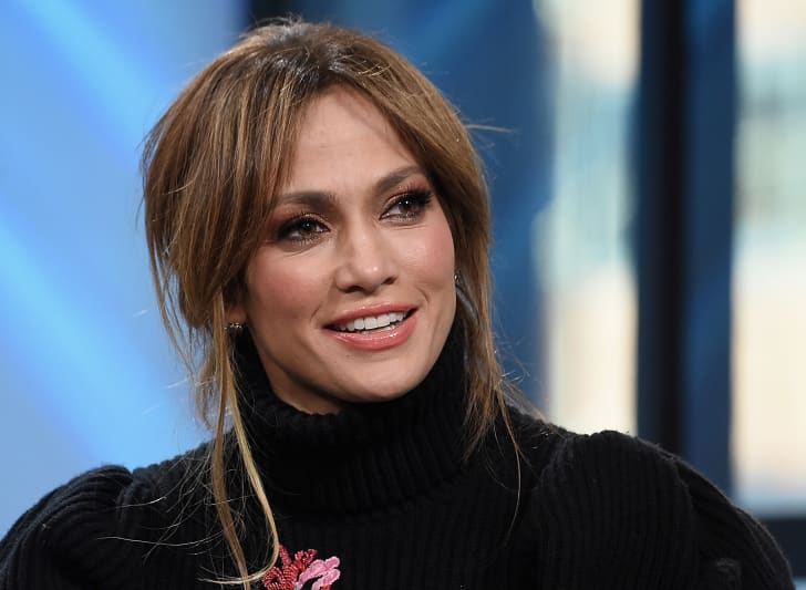 Actress and singer Jennifer Lopez wearing a black, ribbed turtleneck sweater and smiling.