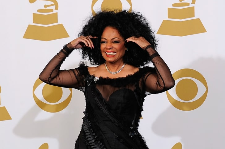 Singer Diana Ross, wearing a formal black dress with sheer sleeves, smiles and lifts her hair back as she stands in front of a  wall emblazoned with Grammy Awards.