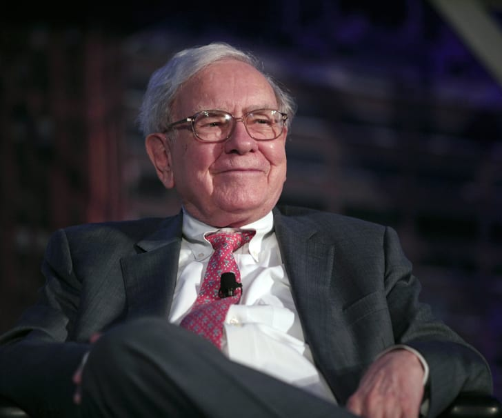 An older man (financial guru Warren Buffett) in a suit, a red tie, and glasses has his leg crossed at the knee and is smiling slightly.