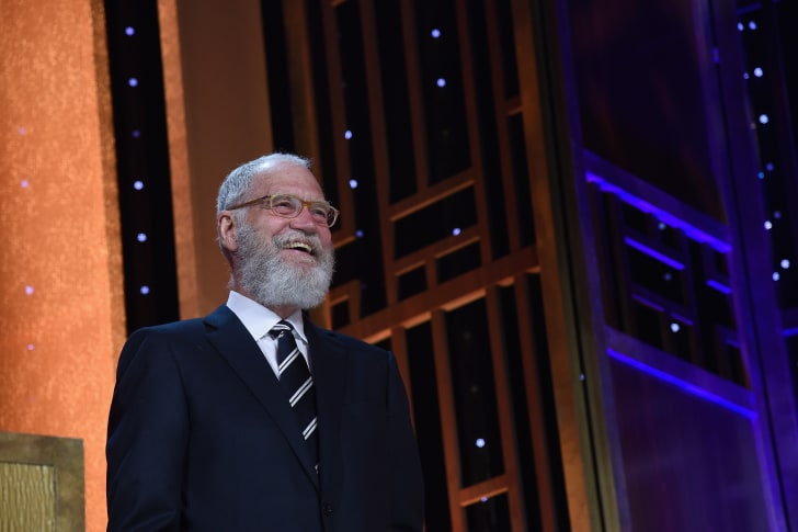 A smiling, bearded man (David Letterman) stands on stage wearing a suit and a striped tie.