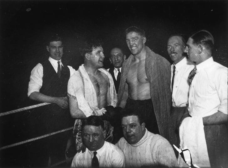 Boxers pose for photo in the ring.