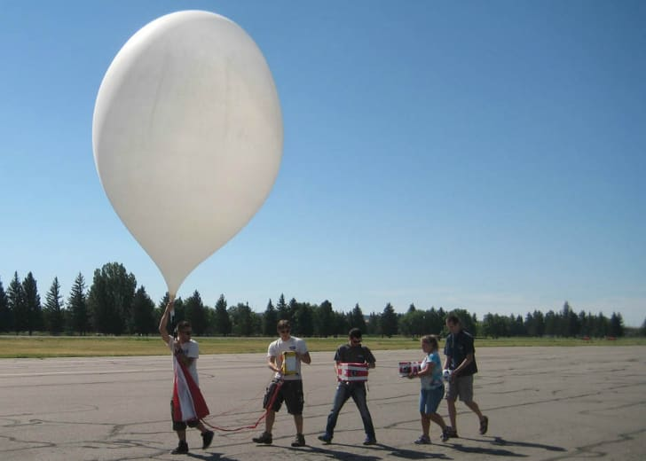 Students carry a large white weather balloon across a tarmac.