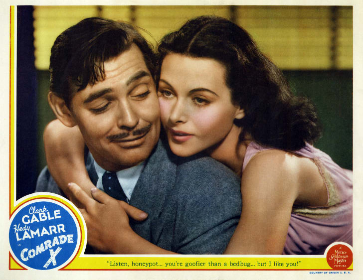 Color lobby card showing Hedy Lamarr embracing a smirking Clark Gable.